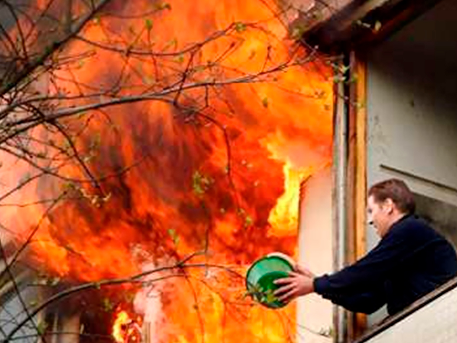 A person trying to put out a fire with a small bucket of water