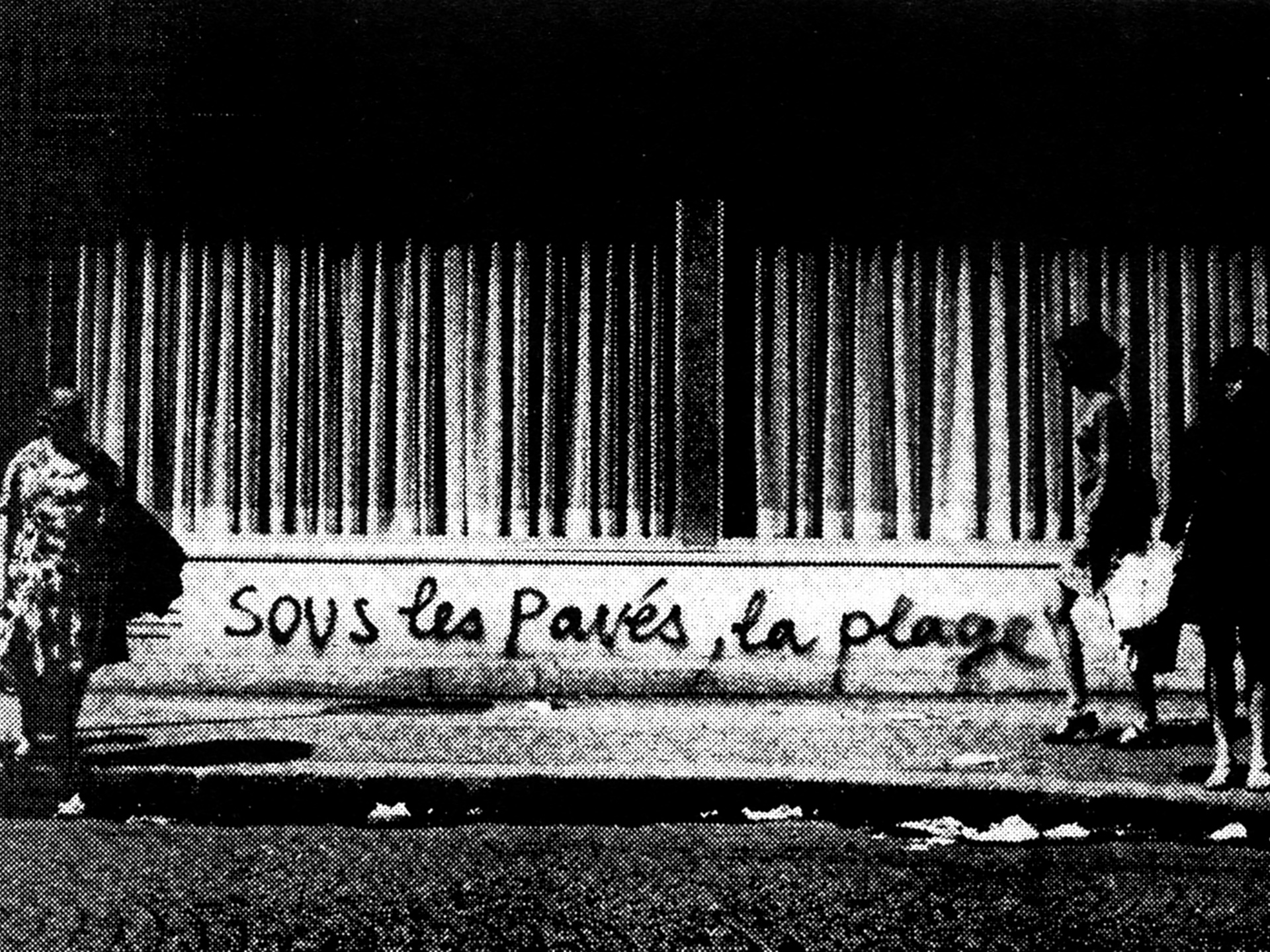 "French street with a tag saying ""sous les pavés, la plage"""