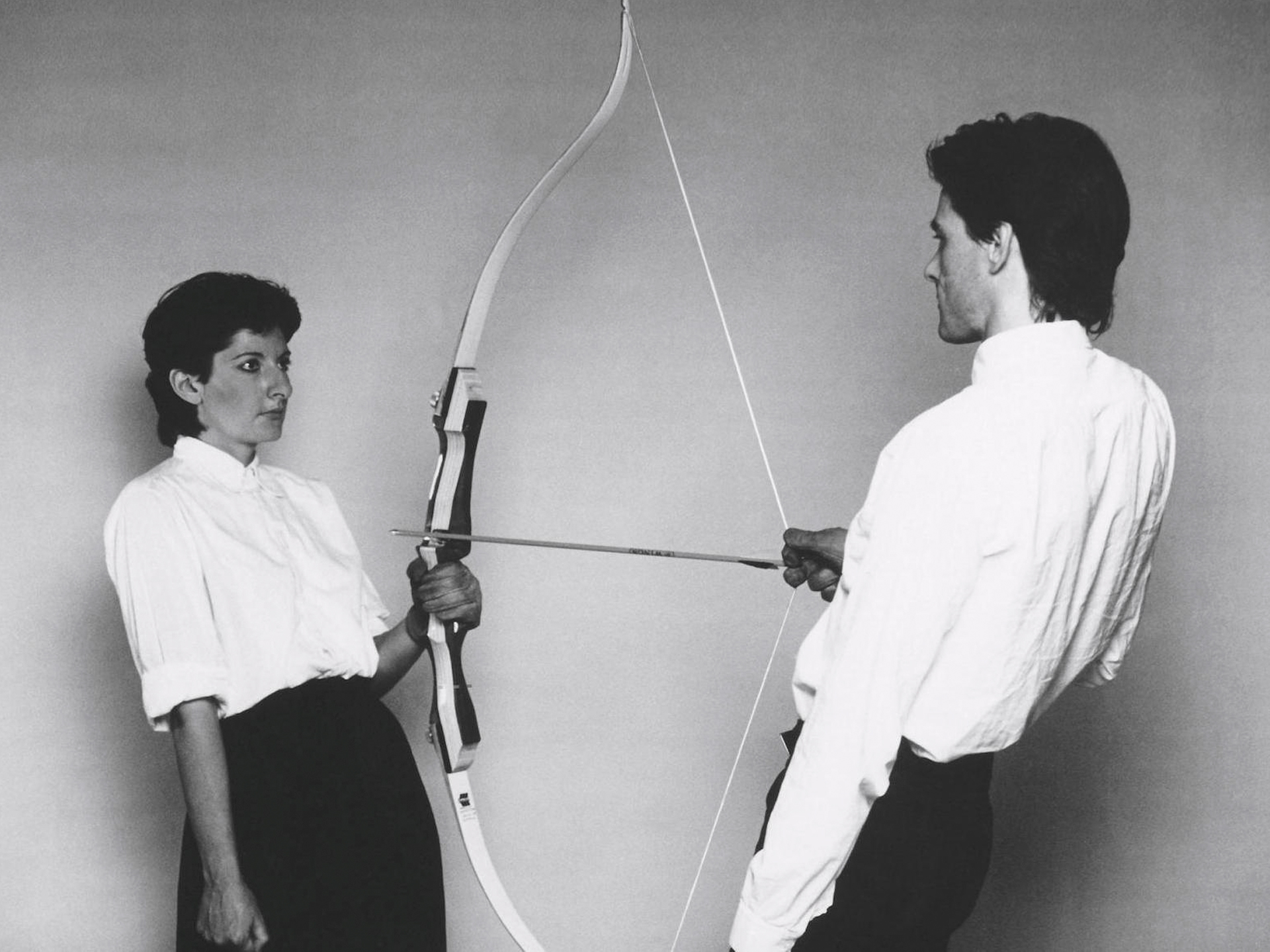 A person holding a bow aimed at a second person
